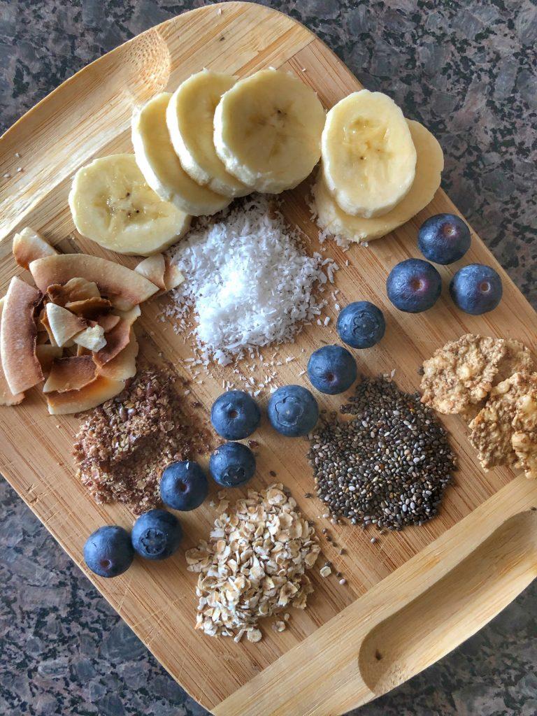 снимка-съставки-продукти-за-веган-чия-пудин-чия-овесени-ядки-кокос-кокосов-чипс-банан-боровинки-ленено-семе-зърнени-закуски-декорация-дъска
